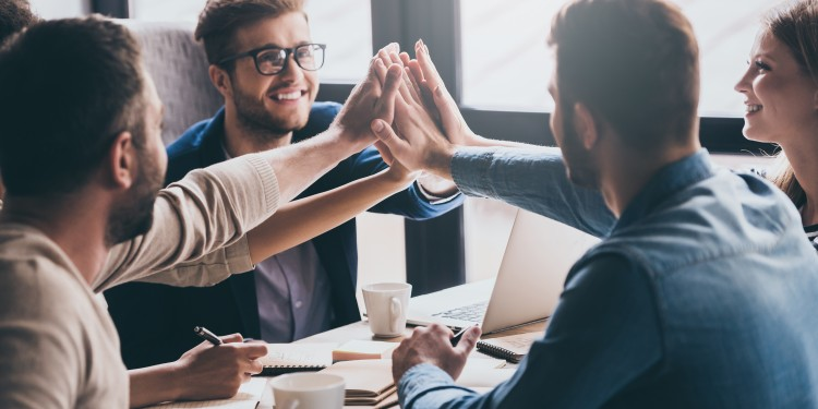 Cheerful young people giving each other high-five with smile while sitting at the office table on business meeting