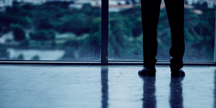 Legs of entrepreneur looking at the city from dark office